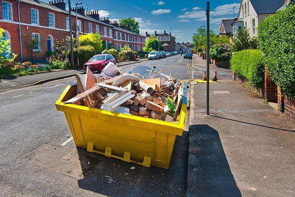 un cassonetto della spazzatura giallo con dentro dei rifiuti in un bellissimo viale con case rosse su entrambi i lati, alberi e cielo azzurro