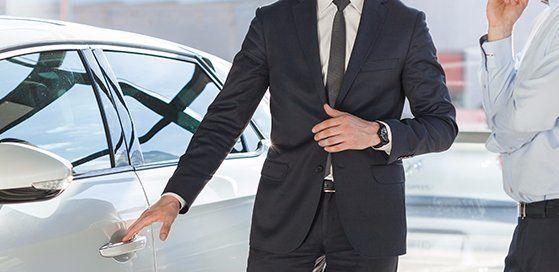 un uomo in giacca e cravatta accanto a una macchina nuova e un secondo accanto a lui con una camicia azzurra