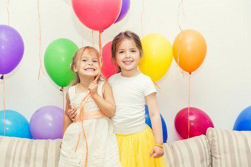 due bambine che sorridono a una festa