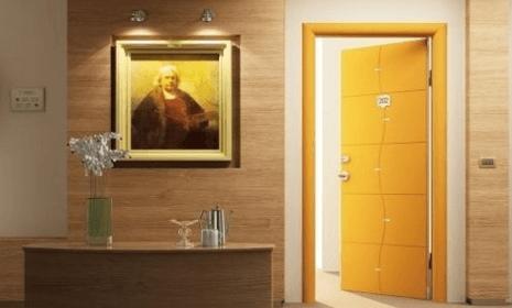 vista interna di porta gialla blindata aperta con vicino un mobile e un quadro appeso al muro
