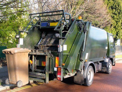 un camion dei rifiuti e un cassonetto