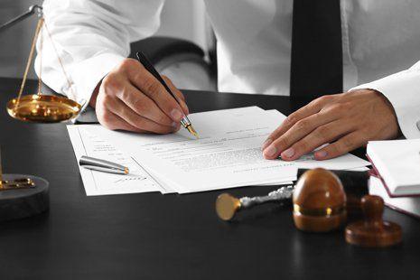 Avvocato mentre firma notaio documenti del pubblico al suo posto di lavoro