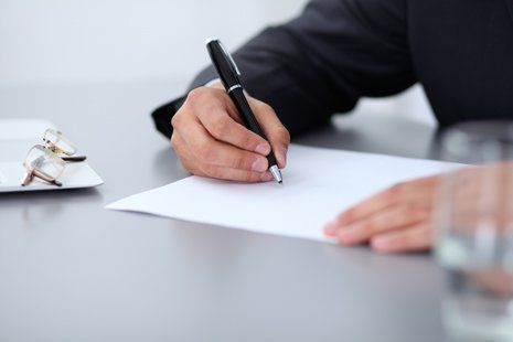 Avvocato mentre firma notaio documenti in ufficio