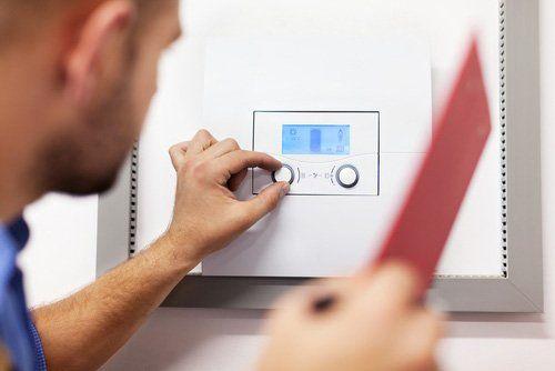 operaio davanti a una caldaia mentre controlla la temperatura