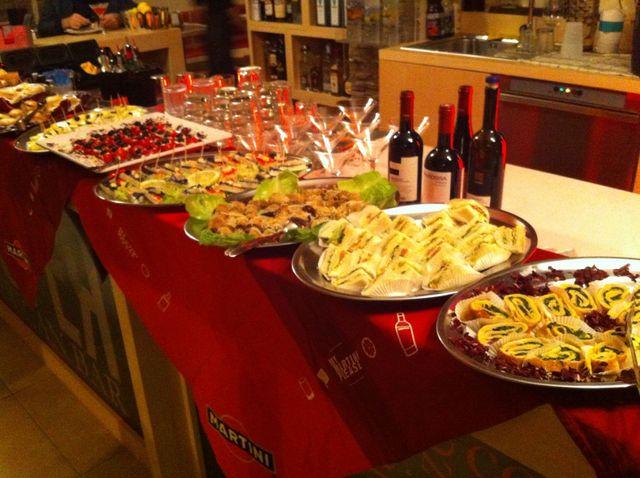 buffet con cibo, bottiglie di vino e bicchieri
