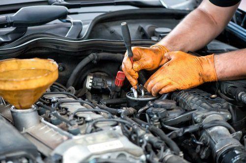 due mani con un cacciavite vicino al motore di una macchina