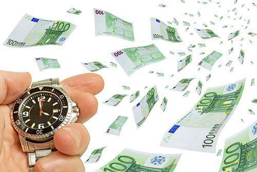 Una mano che tiene un orologio sotto una pioggia  di banconote da 100 euro