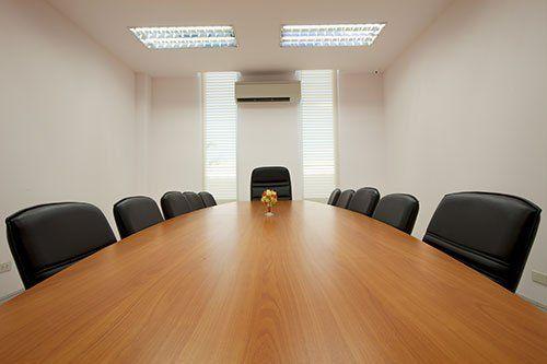 una lunga scrivania con delle sedie in una sala