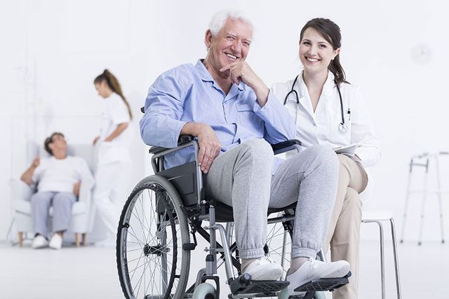 un uomo anziano sorridente su un sedia a rotelle con accanto un infermiera