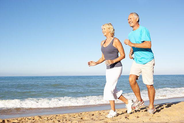 Senior couple jogging on beach and getting plenty of fresh air