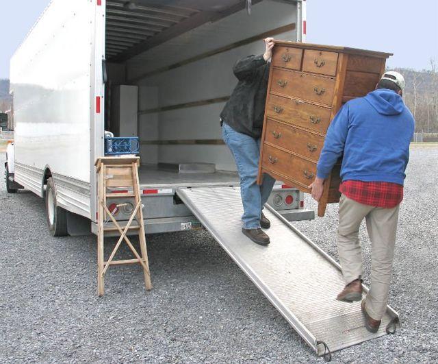 due trasportatori che scaricano un como' in legno da un camion