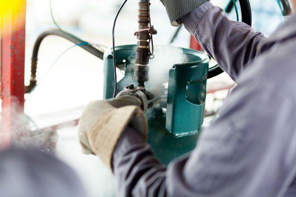 due mani di un operaio che ricarica gas in una bombola