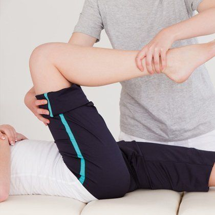 A therapist holding the leg and ankle of a patient to assess movement