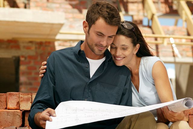 Happy couple standing near building construction