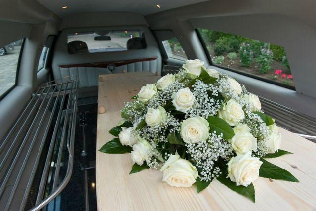 una bara con delle rose bianche sopra in un carro funebre