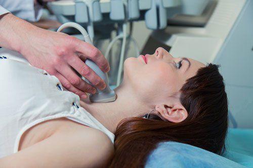una donna sdraiata su un letto durante un'ecografia tracheale