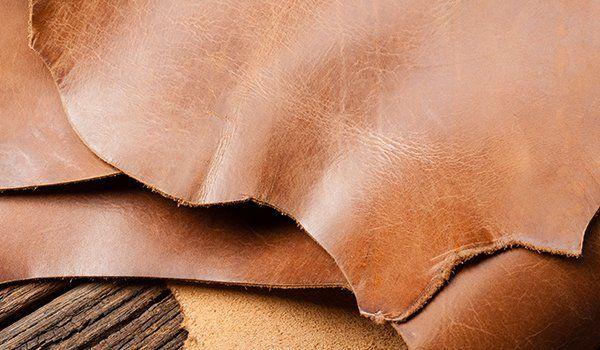 Pelle di color marrone appoggiata su uno sfondo di legno