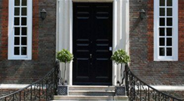 White stone steps with black iron hand rails, leading to a black front door with narrow white windows on either side