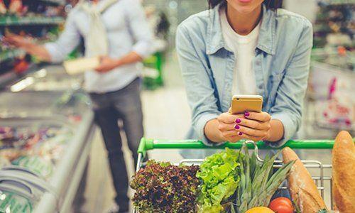 una ragazza che usa il telefono mentre è appoggiata a un carrello della spesa