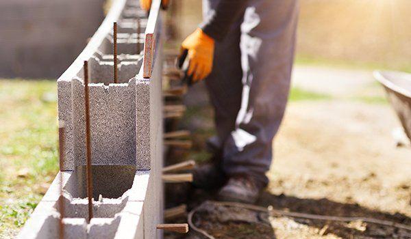 dei tubi in ferro da fondamenta con sopra dei mattoni grigi e un muratore al lavoro