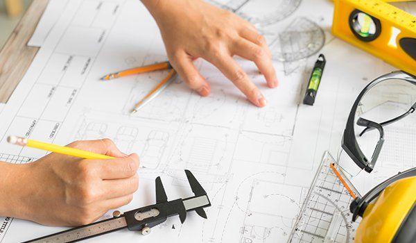 due mani appoggiate su un foglio di un progetto con una matita in mano