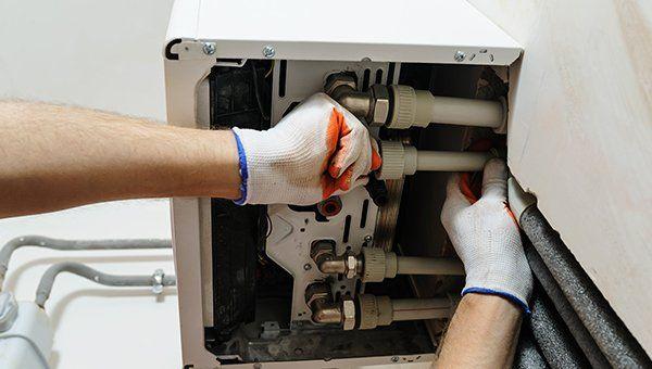 due mani con dei guanti che sistemano dei tubi all'interno di una caldaia
