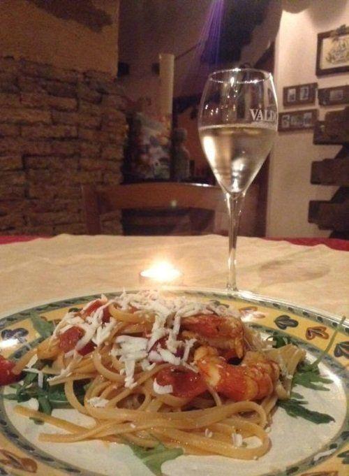 Un piatto di linguine al sugo con gamberi e un bicchiere di vino