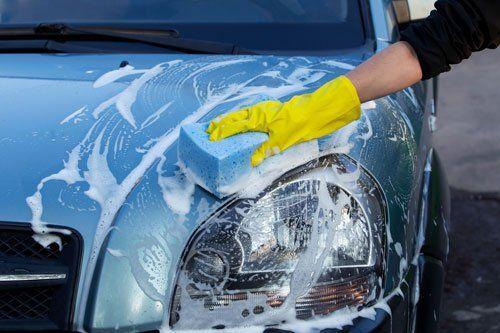 una mano con un guanto che lava una macchina grigia con una spugna insaponata