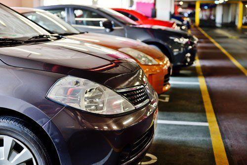 una serie di macchine parcheggiate viste di lato in un parcheggio coperto