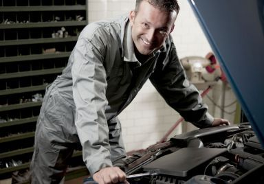 smiling mechanic performing car repairs