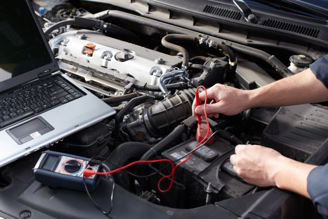 mechanic performs computer diagnostic repairs on a car