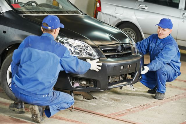 two mechanics assessing car damage in a garage