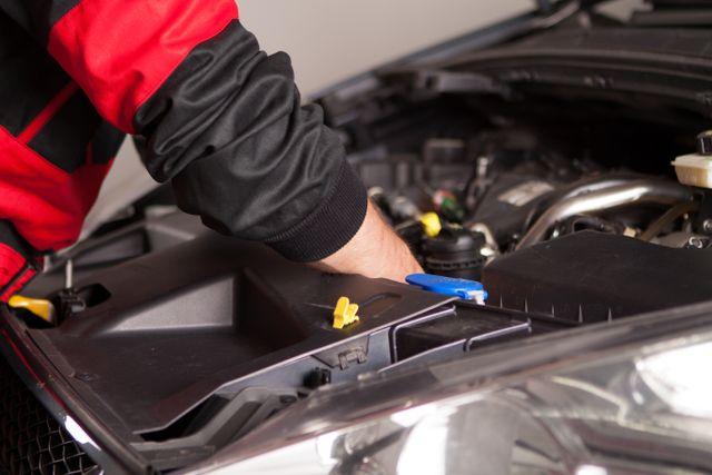 man repairing auto engine