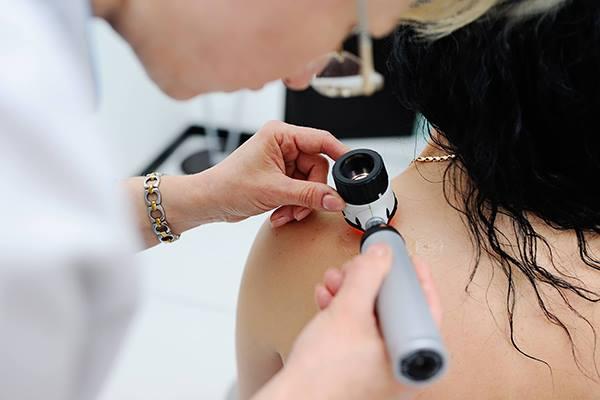 una dottoressa con un un dispositivo medico appoggiato sulla spalla di una donna controllando un neo