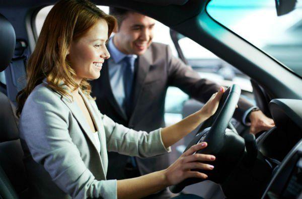 un venditore che mostra una macchina  ad una signora.