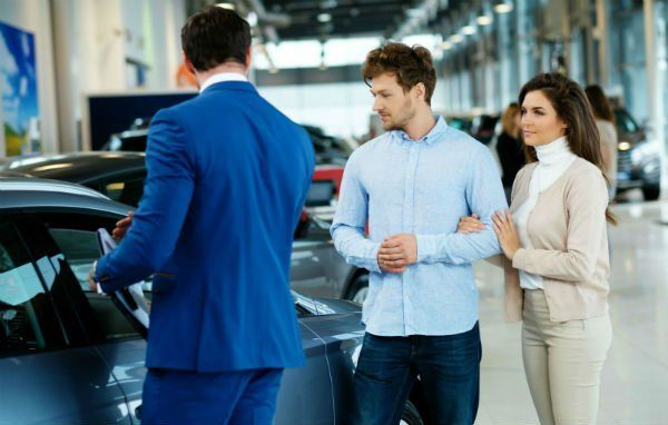 un venditore che mostra una macchina nuova ad una coppia