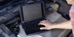 persona mettre batte i tasti di un computer posizionato sopra il cofano di un automobile