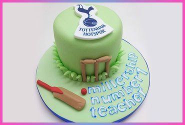 A green cake with cricket bat and ball decoration, and Tottenham Hotspur badge