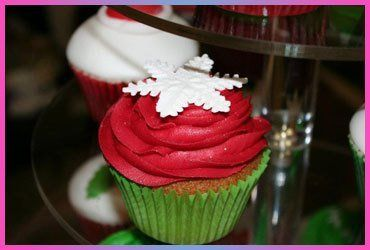 A Christmas cup cake in a green case, with red frosting and white snowflake decoration