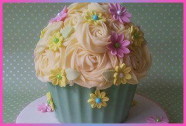 A giant cup cake decorated with sugar flowers