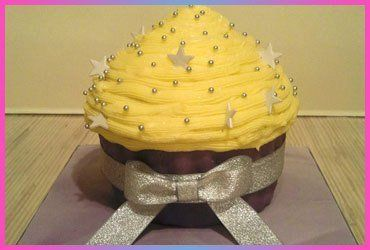 A silver bow tied round a big cup cake with yellow icing and silver stars