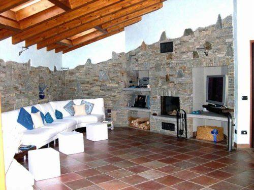 Comfortable sala di stare con pareti di pietra,camino,sofà bianco e cuscini blu e tetto di travi di legno