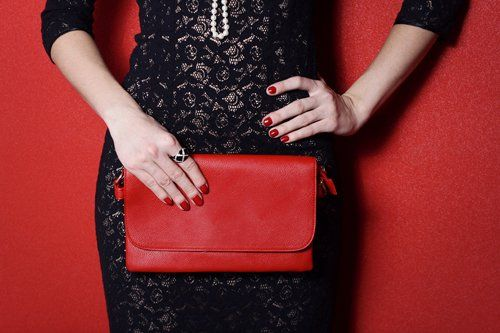 view of a woman wearing black dress and having red purse