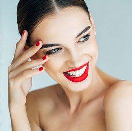 una donna con un rossetto  e smalto di color rosso