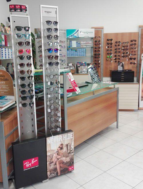 degli occhiali da sole in esposizione su un pannello in un negozio