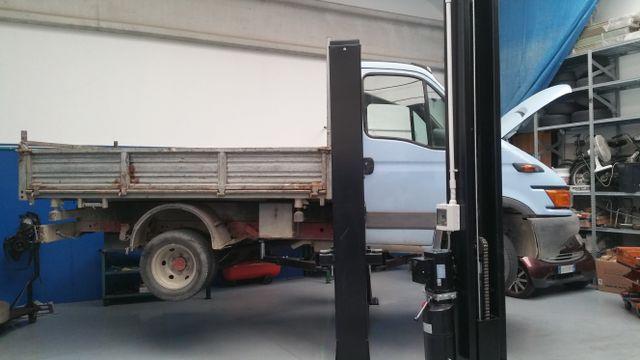 un furgone con cassone sulla piattaforma elevatrice di un'officina
