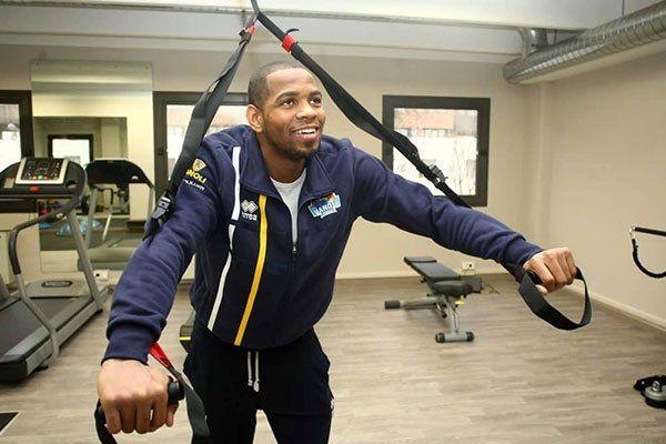 Un uomo con una tuta di color blu mentre fa degli esercizi per le braccia