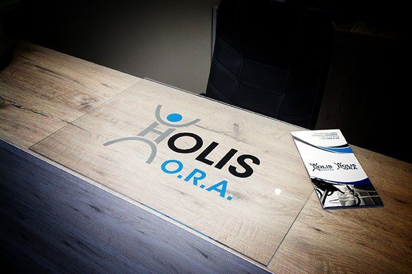 la scritta Holis Ora sul bancone della reception e un volantino
