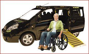 Lady in wheel chair in front of disabled access taxi