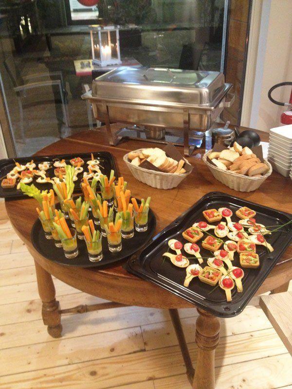 avolo di legno rotondo con sopra dei vassoi con bicchieri con dentro zucchine e carote e coppette con insalata russa e pomodori